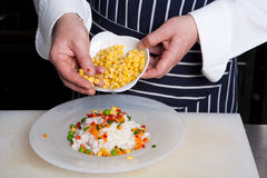 Chef add vegetables to risotto. In a plate Stock Photos