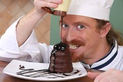 Chef added chocolate sauce at piece of cake Stock Photos
