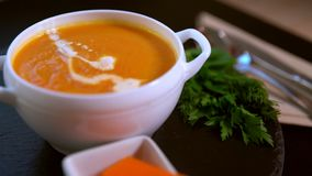 Chef adding cream garnish to pumpkin soup. Chef adding cream garnish to a bowl of freshly made thick pumpkin or butternut soup in a white bowl pouring it from stock video