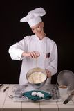 Chef adding egg. Action front view image of a female Pastry Chef adding a fresh egg to her cake batter Royalty Free Stock Photo