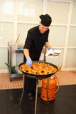 Chef adding the final touch to paella, the shells Royalty Free Stock Photo