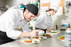Chef Adding Flavors To Food In Kitchen. Smiling professional cook pouring sauce on delicious dish in kitchen royalty free stock images