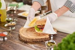 Chef adding french fries to burger. Male chef cooked appetizing burger and french fries. Cooking and food preparing stock photos