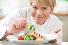 Chef Adding Garnish To Meal In Restaurant Kitchen Royalty Free Stock Images