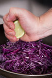Chef adding lemon to cabbage. Chef adding lemon to red cabbage salad Royalty Free Stock Photography