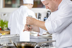 Chef adding pepper on steak in the kitchen Royalty Free Stock Photo