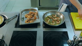 Chef adding salt and garlic to shrimps frying in a pan stock footage