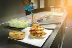 Chef adding sauce on burger Royalty Free Stock Image