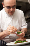 Chef Adding Seasoning To Dish In Kitchen stock images