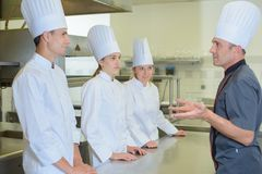 Chef addressing trainee cooks royalty free stock photos