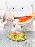 Chef adds chopped tomatoes in a glass bowl Royalty Free Stock Image