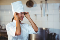 Chef adjusting her hat. While standing in kitchen stock photo