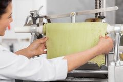 Chef Adjusting Ravioli Pasta Sheet In Machinery Royalty Free Stock Images