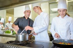 Chef advising cookery student. Chef stock photos