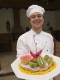 Chef affichant la plaque avec le fruit Image libre de droits