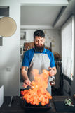 Chef against frying pan with fire, fish cooking Stock Photos