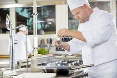 Chef ajoutant le poivre sur le bifteck dans une cuisine professionnelle Images stock