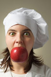 Chef with an apple in her mouth Royalty Free Stock Images