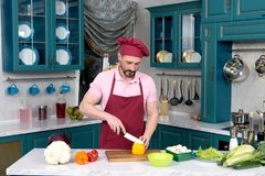 Chef in apron and bonnet cutting yellow paprika for salad. On cutting board. Man loves paprika in fresh vegetable salad. Secret ingredient preparing at kitchen Stock Photography
