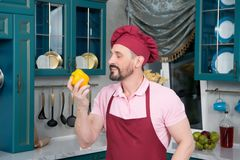 Chef in apron and cap sniffing yellow paprika and smile. Bearded. Bearded chef in apron and cap sniffing yellow paprika and smile. Cook holds paprika in hand Royalty Free Stock Photos