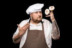 Chef in apron and hat holding doughnuts on fingers. Isolated on black Royalty Free Stock Photos