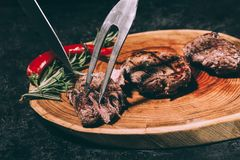 Chef in apron with meat fork and knife slicing gourmet grilled steaks with rosemary and chili pepper on wooden board. Close-up view of meat fork and knife royalty free stock images