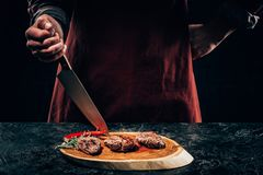 Chef in apron with meat fork and knife slicing gourmet grilled steaks with rosemary and chili pepper on wooden board. Cropped shot of chef in apron standing with royalty free stock images