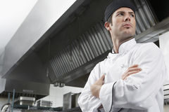Chef With Arms Crossed In Kitchen Stock Photo