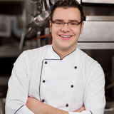 Chef With Arms Crossed Standing In Commercial Kitchen. Portrait of confident chef with arms crossed standing in commercial kitchen royalty free stock photos