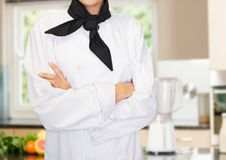 Chef arms folded against blurry kitchen Royalty Free Stock Image