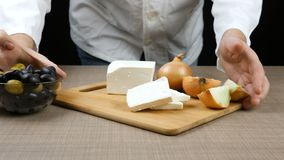 The chef arranges a table made up of cut pieces of cheese, two onions of which one is cut, an olive bowl and a tomato. The chef arranges a table made up of cut stock footage