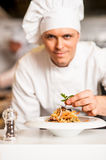 Chef arranging pasta salad in a white bowl Stock Photography