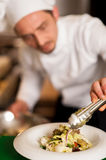 Chef arranging tossed salad in a white bowl Royalty Free Stock Photo