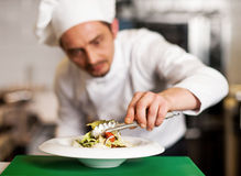 A chef arranging tossed salad in a white bowl Stock Photography