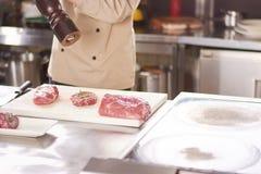 Chef arrosant le poivre moulu sur le bifteck Images libres de droits