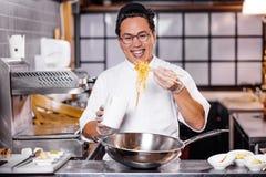 Chef asiatique avec la nouille dans la cuisine photographie stock