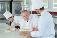 Chef assessping pudding made by trainee chef. Chef stock photography