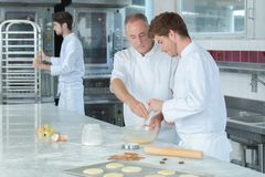 Chef assistant learning to make dough stock photography