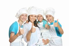 Chef with assistants showing thumbs up. Smiling female chef with assistants showing thumbs up royalty free stock images