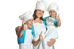 Chef with assistants showing thumbs up. Smiling female chef with assistants showing thumbs up royalty free stock photo
