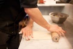 Chef avec la pâte de roulement de roulement-goupille à la cuisine Photo libre de droits