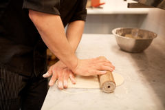 Chef avec la pâte de roulement de roulement-goupille à la cuisine Images stock