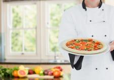 Chef avec la pizza contre la cuisine trouble avec des légumes photos stock