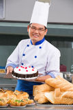 Chef or baker. Baker holding the tart in commercial kitchen royalty free stock image