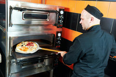 Chef baker cook putting pizza in the oven Royalty Free Stock Photography
