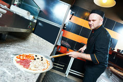 Chef baker cook putting pizza in the shove Royalty Free Stock Photography