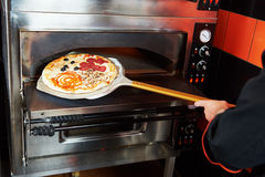 Chef baker cook taking out pizza from the oven Royalty Free Stock Images