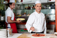 Chef baker making pizza at kitchen royalty free stock image