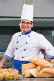 Chef or baker posing in front of the pastries Stock Photos