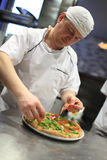 Chef baker in white uniform making pizza at kitchen Royalty Free Stock Photos